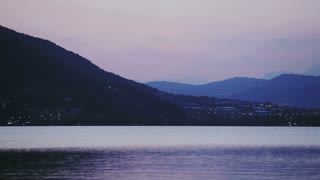 Lake Lago di Caldonazzo in Northern Italy - panning footage (left to right) on a late summer evening with mountain hills in the distance.