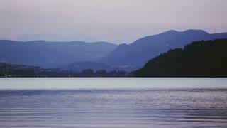 Lake Lago di Caldonazzo in Northern Italy - static footage on a late summer evening with mountain hills in the distance.