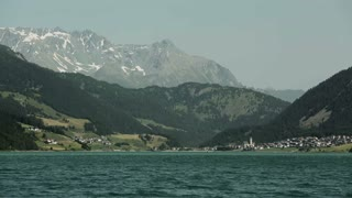 Lake Lago di Resia, also known as Reschensee by summer and its surrounding mountaintops. Telephoto static footage.