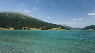 Lake Lago di Resia, also known as Reschensee by summer with blue sky and surrounding mountains.