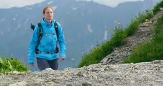 Long shot of a young woman hiking on a mountain trail.