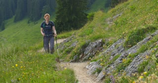 Long shot of a young woman hiking on a narrow mountain trail by summer.