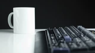 Low angle dolly shot of a black computer keyboard and a whit coffee mug on top of a white office desk. Gradual focus move - starts at the mug; ends at the Enter key.