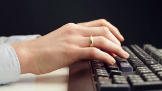 Low angle, side view dolly shot of a young businesswoman typing on a black computer keyboard on a white office desk.