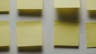 Many yellow sticky notes on an office wall. Closeup vertical dolly shot.