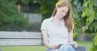 Medium shot of a redhead woman reading an e-book on a tablet in a city park.