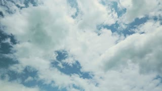 Panning footage of blue sky with white clouds with sunlight.
