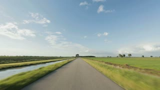 Point-of-view footage from a car driving on an empty rural road, surrounded by green fields.