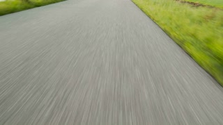 Point of view footage of a vehicle moving fast over a narrow asphalt road, surrounded by green grass.