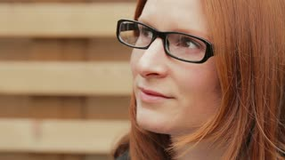 Portrait of a young business woman wearing glasses, looking to her side and then smiling at the camera.