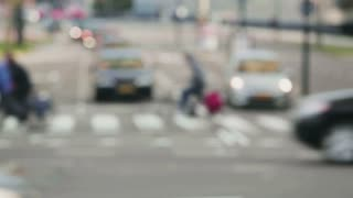 Real time abstract footage of cars and bicycles passing through a busy city intersection.