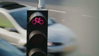 Red cyclist traffic light with city traffic on a street behind it, static footage.