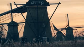 Scenic Dutch windmills at Kinderdijk by sunset.