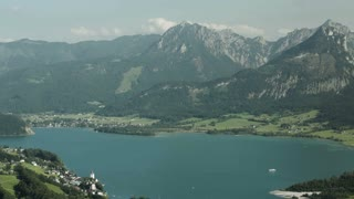 Scenic panorama pan over the Wolfgangsee lake in Austria with a view at the surrounding mountaintops on a warm summer day.