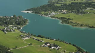 Scenic panorama pan over the Wolfgangsee lake in Austria with the surrounding villages and settlements.