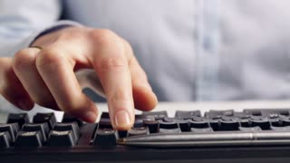 Sliding shot of a young businesswoman typing on a black computer keyboard. Closeup from a low angle.