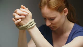 Slow motion medium shot of praying woman breaking free from a rope tying her hands together. Dramatic lighting.