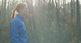 Slow motion portrait of a female athlete in a forest.