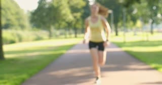 Slow motion shot of  a female runner using a sport smartwatch in a park while jogging.