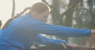 Slow motion shot of a woman stretching after jogging in a park.