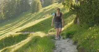 Slow motion shot of a young woman ascending a mountain hill on a narrow trail.