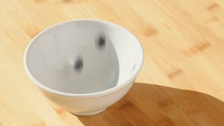 Slow motion shot of blueberries falling in a white bowl.