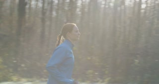 Slow motion tracking shot of a woman jogging in a forest on a cold morning.