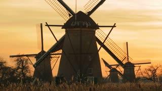 Spinning Dutch windmills by sunset. Kinderdijk, the Netherlands.