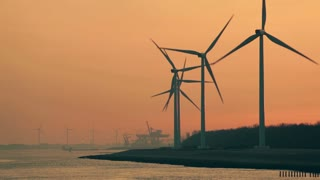 Spinning wind power turbines along a sea shore by sunrise or sunset.
