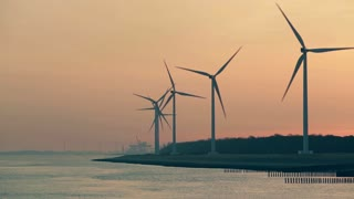 Spinning wind turbines along a sea shore by sunrise or sunset.
