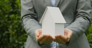 The camera pans across a closeup shot of a business woman holding a paper model house in her hands.
