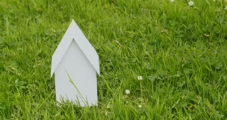The camera pans over a white paper house on a green grass field. Mortgage or new home concept.