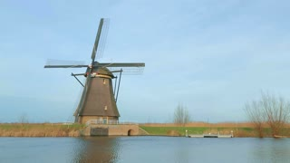 The camera pans to reveal a row of historic windmills at Kinderdijk, Holland.
