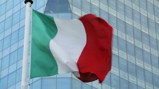 The flag of Italy waving before an office building with a glass facade.