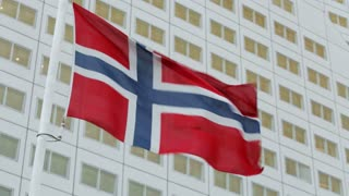 The flag of Norway waving before an office building with many windows.