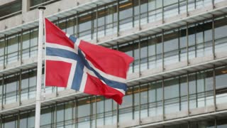 The flag of Norway waving before an office building.