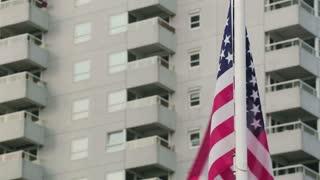 The United States of America national flag on a pole with a residential building behind it.