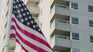 The United States of America national flag waves on a pole with a residential building behind it.