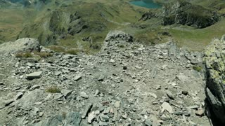 Tilt footage reveals a scenic view over hills, lakes and mountaintops in the Rila mountain, Bulgaria by summer.