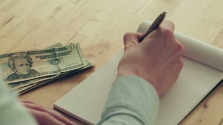 Top and closeup view of a woman doing finances - writing budgets down on a paper notebook next to a stack of dollar bills.