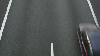 Top view of cars driving fast on a two lane highway.