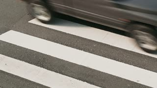 Top view of cars driving over a zebra crossing on a city street with camera panning motion.