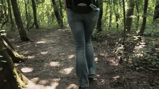 Tracking footage of a female tourist with a backpack walking on a forest trail by summer.