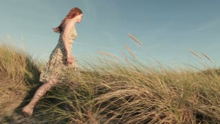 Tracking footage of a young woman walking among dune grass on a beach by summer.