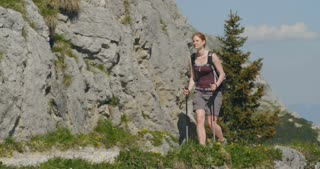 Tracking long shot of a young woman hiking alone on a mountain trail by summer.