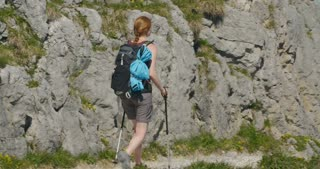 Tracking shot of a woman on a day hike on a mountain trail by summer.