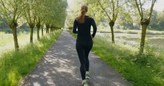 Tracking shot of a young woman jogging alone in a park.