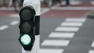 Traffic light for cyclists changes signals on a busy urban intersection.