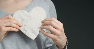 Valentine's day concept - a young woman holds a wooden heart close to her body.