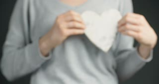 Valentine's day concept - a young woman holds a wooden heart to the camera.